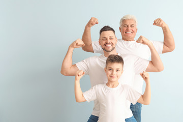 Man with his father and son showing muscles on color background