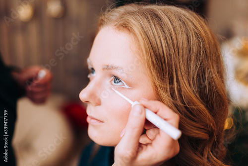 Makeup artist makes white fantasy makeup for a young woman with brown hair Canvas Print