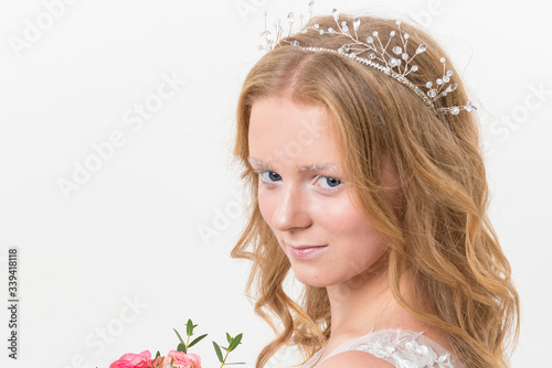 Portrait of romantic young bride in white lace wedding dress with fantasy makeup and wavy blonde hair with wedding bouquet in her hands getting ready in bride's morning Canvas Print