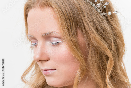Photo Portrait of romantic young bride in white lace wedding dress with fantasy makeup and wavy blonde hair