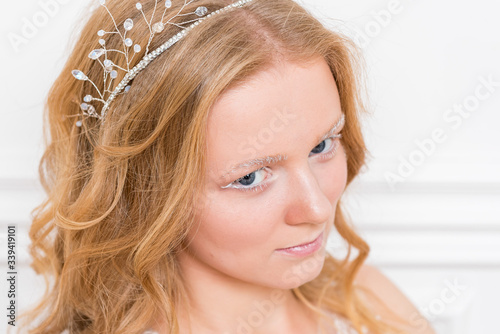 Photo Romantic young bride in elegant hotel room in white lace wedding dress with makeup and wavy blonde hair with pearl jewelry getting ready in bride's morning