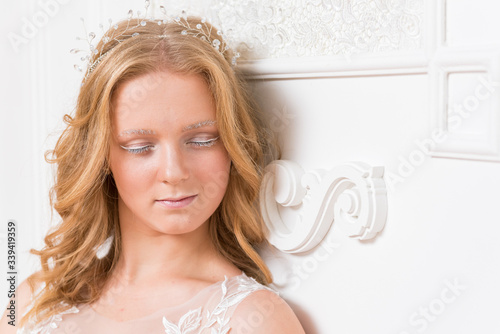 Photo Romantic shy young bride in elegant hotel room in white lace wedding dress with makeup and wavy blonde hair with pearl jewelry getting ready in bride's morning