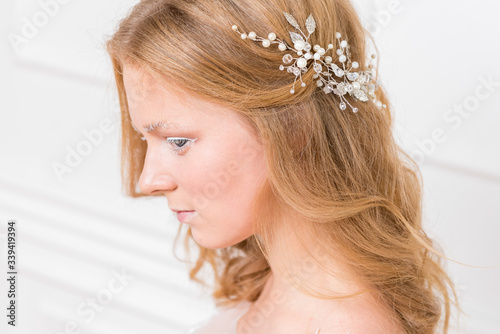 Romantic shy young bride in elegant hotel room in white lace wedding dress with makeup and wavy blonde hair with pearl jewelry getting ready in bride's morning Canvas Print