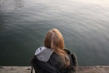 Rear View Of Woman Sitting Against Lake