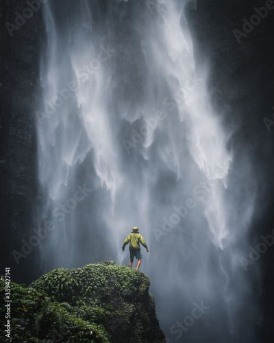 Man standing by a waterfall in Java - 339427141