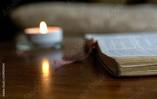 Fotografiet Open bible with burning candle on the table