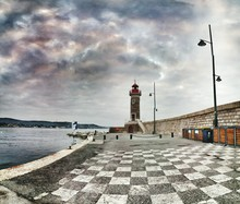 Lighthouse With Checked Pattern Footpath Against Cloudy Sky