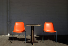 Empty Chairs With Table On Sidewalk Against Wall