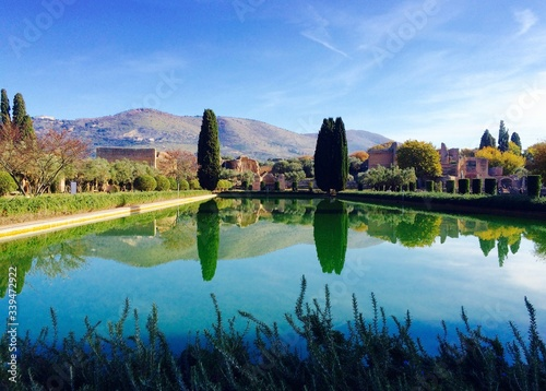 Fototapeta Trees And Mountains Reflecting In Pond At Hadrian Villa