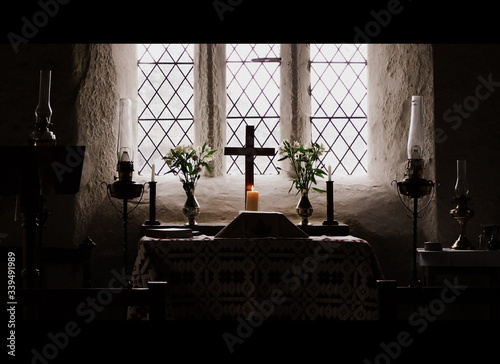 Canvas Print Illuminated Candles With Cross On Altar Against Window At Church