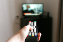 Hand Of A Man With A Remote Control From The TV.