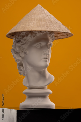 Leinwand Poster White plaster Statue of a bust of Apollo Belvedere in an Asian conical hat