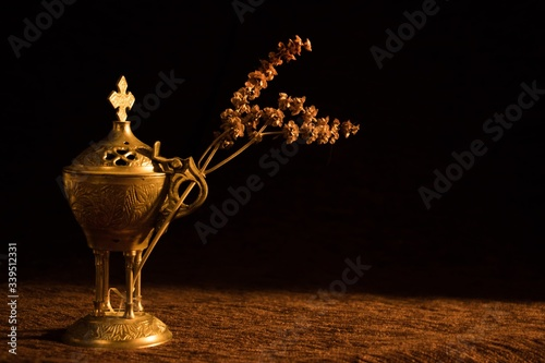 Photo Beautiful church censer with a dried branch with a dark background