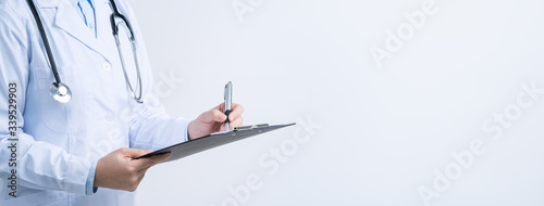 Photo Doctor with stethoscope in white coat holding clipboard, writing medical record diagnosis, isolated on white background, close up, cropped view