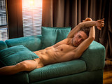 Handsome totally naked muscular young man laying down on couch at home in seductive attitude, looking at camera