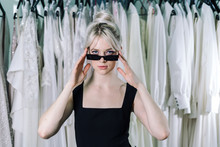 Beautiful Girl In Black Dress And Black Sunglasses, Stands On The Background Of Dresses Hanging On A Hanger.
