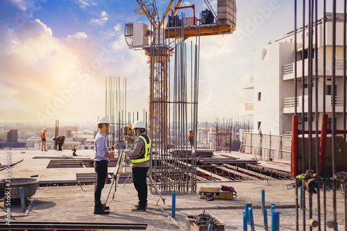 Obraz Engineer and surveyor worker working with theodolite transit equipment at outdoors construction site. - fototapety do salonu