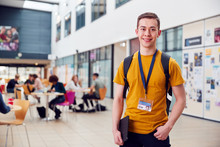 Portrait Of Smiling Male College Student In Busy Communal Campus Building