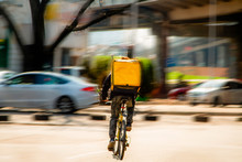 Courier On A Bicycle To Pick Up And Deliver An Order From The Fast Food Restaurant. Photo In Motion. Coronavirus Outbreak.