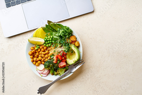 Valokuva Flatlay with a laptop and a healthy vegetarian lunch bowl with avocado, chickpeas, quinoa and vegetables, garnished with microgreens and nut dressing