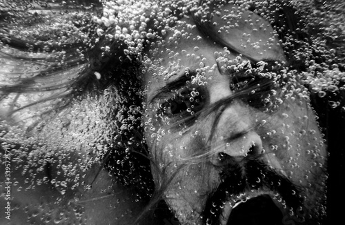Photo Artistic pic out of focus underwater with long hair man swimming with bubble in