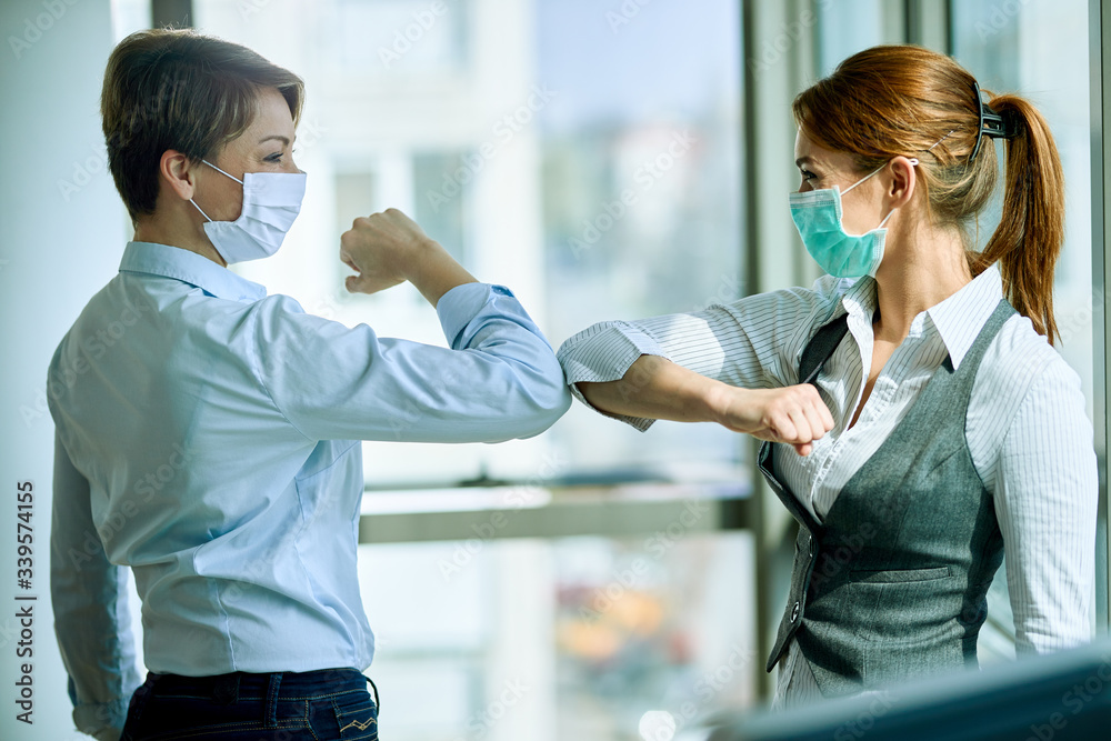 Fototapeta Female colleagues with face masks elbow bumping while greeting in the office.