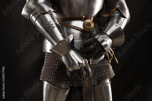 Mannequin man with a beard in a helmet and armor of a knight posing on a black b Wallpaper Mural