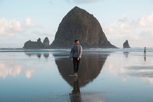 Male Traveler Walking Along The Water At Canon Beach Oregon