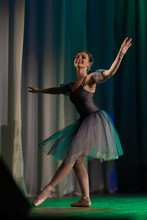 Young Girl Ballerina In A Gray Dress Dancing Ballet Performance On Stage In A Theater On A Green Background