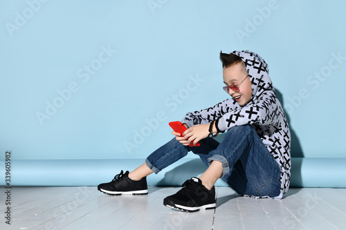 Photo Kid in sunglasses, blue jeans and hoodie, black bracelet, sneakers