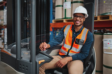 Smiling Forklift Driver With Spectacles Sitting In Vehicle In Warehouse Looking At Camera Wearing A White Helmet And Safety Vest