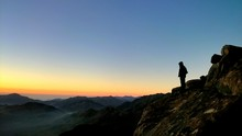 Silhouette Man Standing On Mountain Against Clear Sky During Sunset