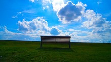 Empty Bench On Grassland Against The Sky