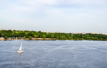 Beautiful Summer Landscape View Of Sailboat Floating On Water Along The River Bank Dnipro River In Kyiv, Ukraine.