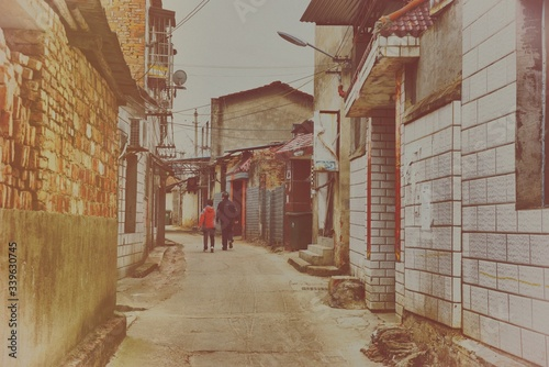 Papel de parede Rear View Of Man And Woman Walking In Alley