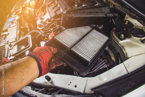 Car air filter in a hand of mechanic man is installing into air filter socket of car engine,Automotive part concept Canvas Print