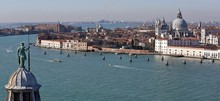 Canal By Santa Maria Della Salute In City On Sunny Day
