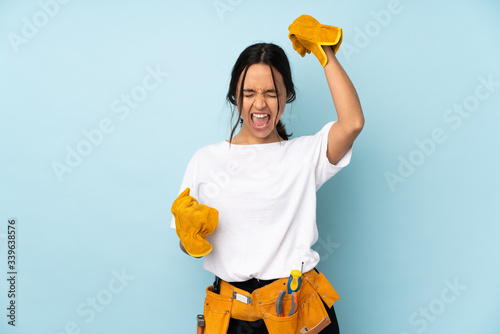 Young electrician woman isolated on blue background celebrating a victory Fototapet