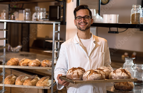 Fotografie, Obraz Portrait of young male baker holding bread in his hands at bakery