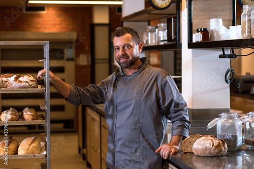 Leinwand Poster Portrait of mid age male baker at bakery.