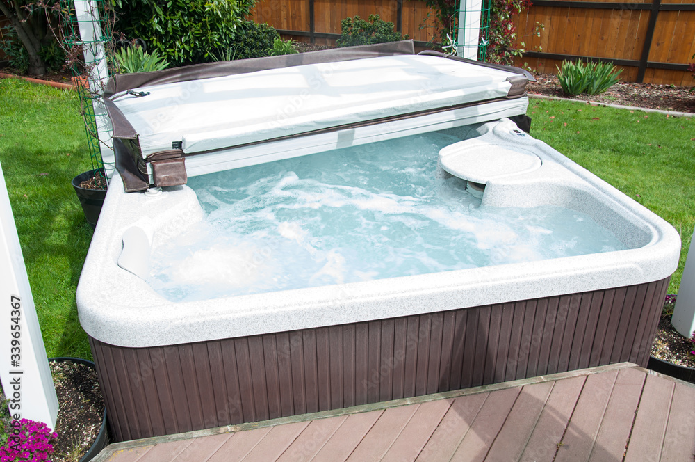 Fototapeta Hot tub in back yard with water bubbling and the lid half off, ready to be enjoyed in the outdoors.