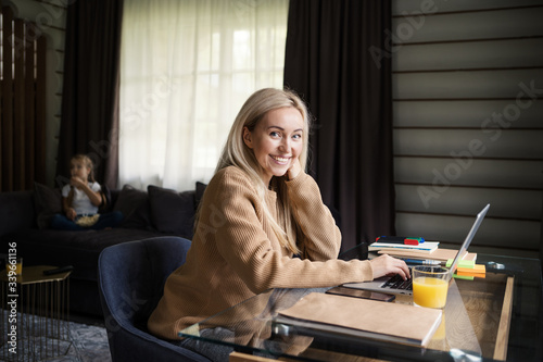 Obraz Beautiful blonde woman looking at camera and smiling while working on laptop computer sitting at desk at home, her little daughter eating popcorn and watching tv on sofa in background - fototapety do salonu