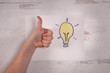 Real human hand giving a thumbs up next a doodled hand drawn bright lit up a lightbulb flat lay design background