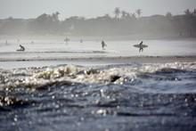 Surfers Walking At Beach