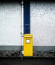 Yellow Mailbox Against Wall