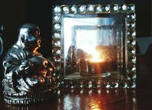 Laughing Buddha Statue By Mirror With Lit Candle Reflection