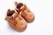 Pair of brown leather kids shoes on white background.