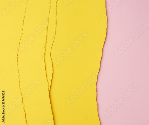 Fototapeta background of layered yellow torn paper with a shadow on a pink background obraz