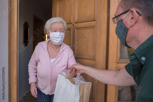 Photo Senior woman with face mask gets neighborhood shopping assistance