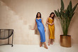 canvas print picture - Two pretty beautiful woman brunette hair natural makeup wear fashion clothes sexy silk long dress midi style date party walk sandals interior studio stairs flowerpot summer journey romantic friends.
